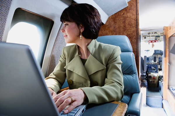 Waist-length view of a businesswoman using a laptop on a private airplane and looking out of the window