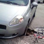 Auto ferma in mezzo all'incrocio: bloccata in un cratere aperto sulla strada